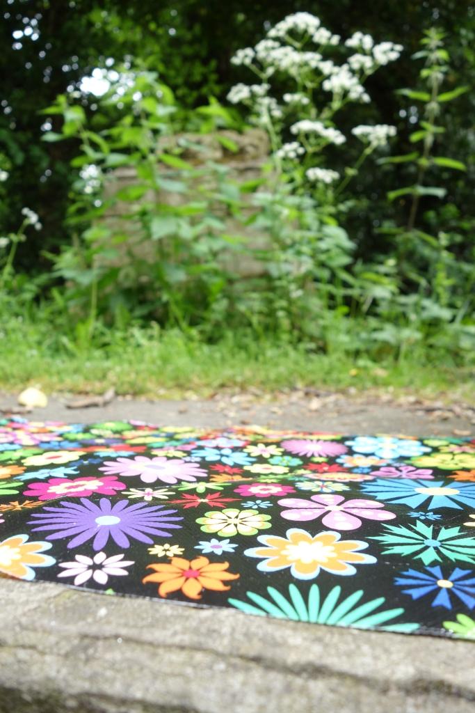 A colourful mat on a gravestone.