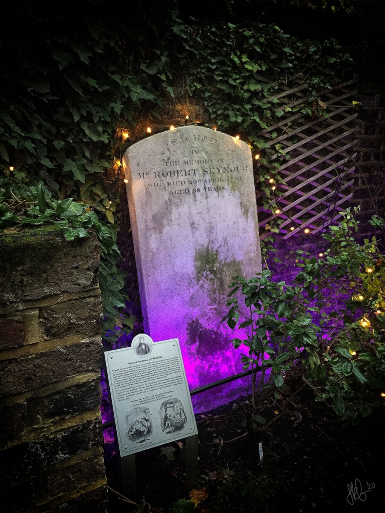 A simple tall headstone with a string of fairy lights around the top, against an ivy-covered wall.